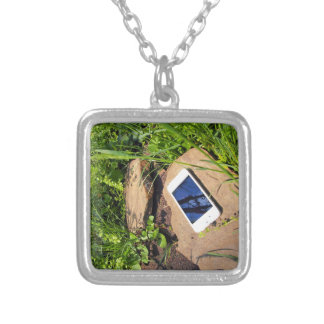 Smartphone on a rock in a meadow square pendant necklace