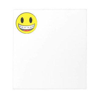 Smiley con los apoyos bloc de papel