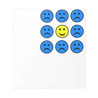 Smiley feliz en una muchedumbre de caras infelices libretas para notas