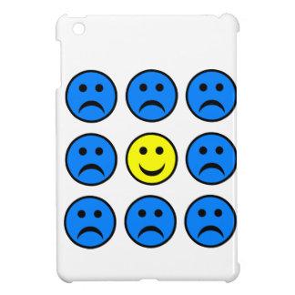 Smiley feliz en una muchedumbre de caras infelices