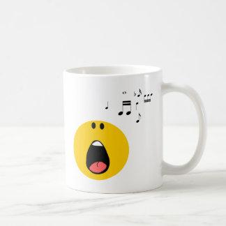 Smiley que canta su poco corazón hacia fuera taza básica blanca