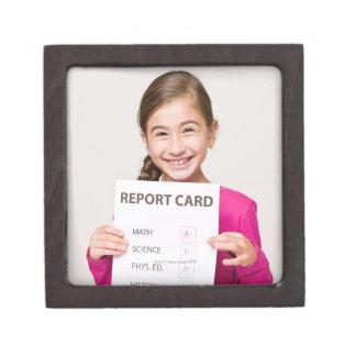 Smiling girl student proud of report card keepsake box