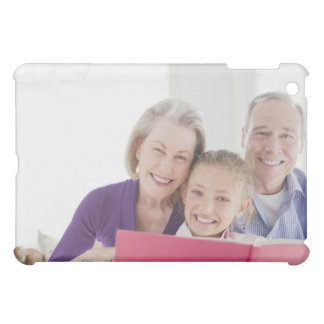 Smiling grandparents reading cookbook with iPad mini covers