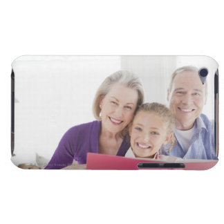 Smiling grandparents reading cookbook with iPod touch cover