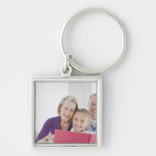 Smiling grandparents reading cookbook with keychain