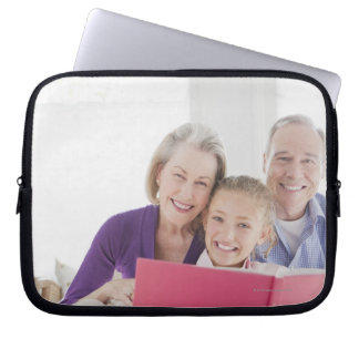 Smiling grandparents reading cookbook with computer sleeve