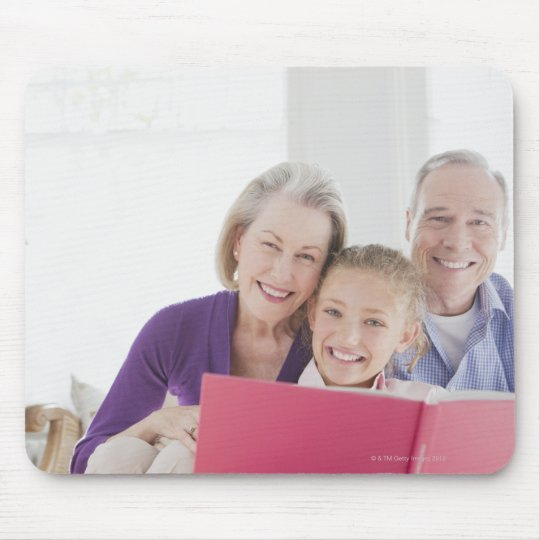 Smiling grandparents reading cookbook with mouse pad