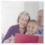 Smiling grandparents reading cookbook with large square tile