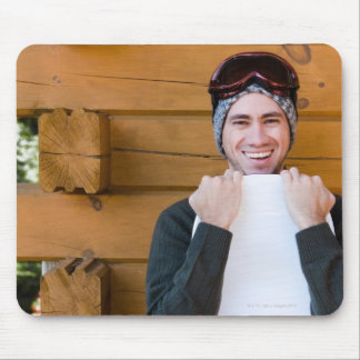 Smiling man posing with snowboard outside cabin mouse pad