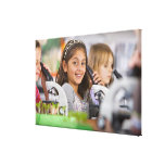 Smiling students peering into microscopes in canvas print