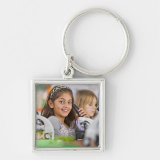Smiling students peering into microscopes in key chains