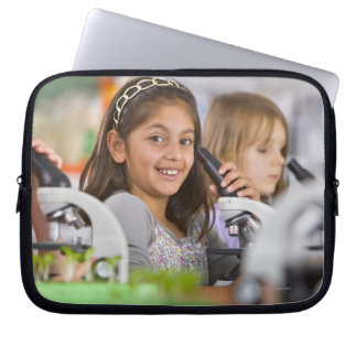 Smiling students peering into microscopes in laptop sleeve