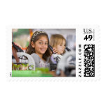Smiling students peering into microscopes in stamps