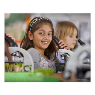 Smiling students peering into microscopes in poster