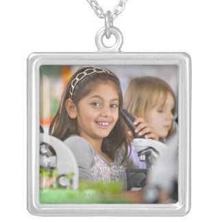 Smiling students peering into microscopes in silver plated necklace