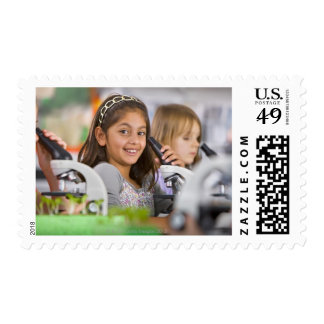 Smiling students peering into microscopes in stamp
