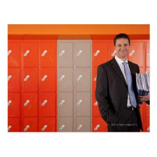 Smiling teacher holding paperwork near school postcard