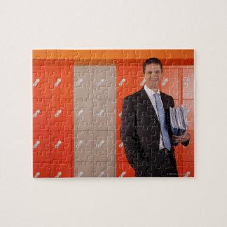 Smiling teacher holding paperwork near school jigsaw puzzle
