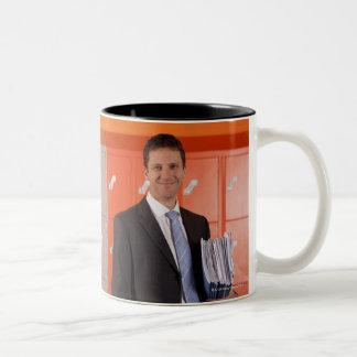 Smiling teacher holding paperwork near school Two-Tone coffee mug