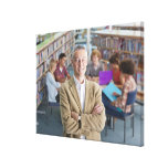 Smiling teacher standing in school library with canvas print