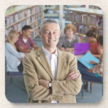 Smiling teacher standing in school library with coaster