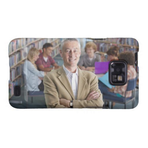 Smiling teacher standing in school library with galaxy s2 case