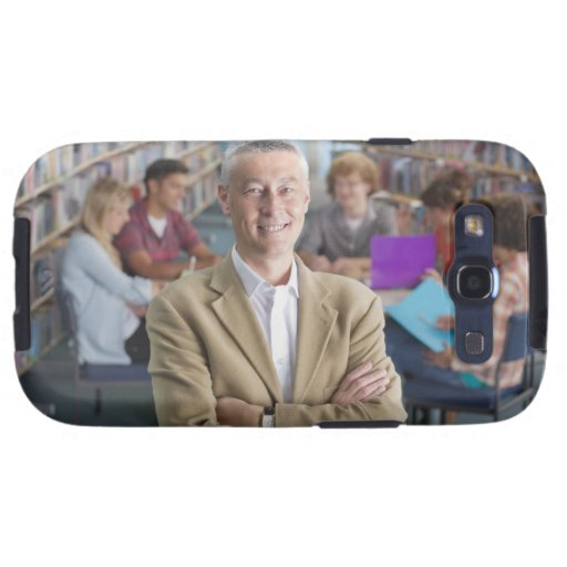 Smiling teacher standing in school library with galaxy SIII cases