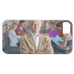 Smiling teacher standing in school library with iPhone SE/5/5s case
