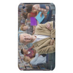 Smiling teacher standing in school library with iPod touch case