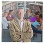 Smiling teacher standing in school library with large square tile