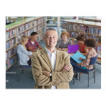 Smiling teacher standing in school library with postcard