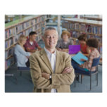 Smiling teacher standing in school library with poster