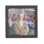 Smiling teacher standing in school library with premium keepsake boxes