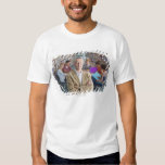 Smiling teacher standing in school library with tshirts