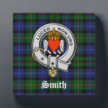 "Smith Family Tartan Plaid and Clan Crest Badge Plaque<br><div class=""desc"">This stunning Scottish heritage inspired decorative plaque has the Smith family tartan plaid pattern in blue, green with red and yellow stripes as a background. The Smith Clan Crest Badge is shown with a silver color strap and buckle, blue and yellow wreath and a flaming winged heart. The clan motto...</div>"