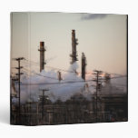 Smoke stacks and distillation towers rise 3 ring binders