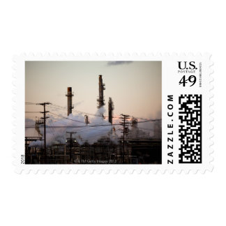 Smoke stacks and distillation towers rise stamps