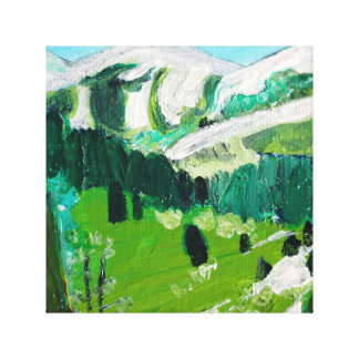 Snow capped mountains in a green valley canvas print