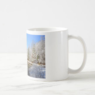 Snow covered landscape around the pond coffee mug