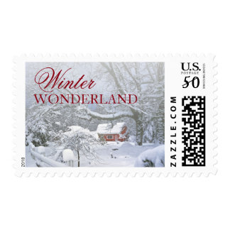 Snow covers landscape and red barn in distance. postage