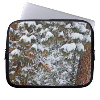 Snow fills the boughs of ponderosa pine trees laptop computer sleeves
