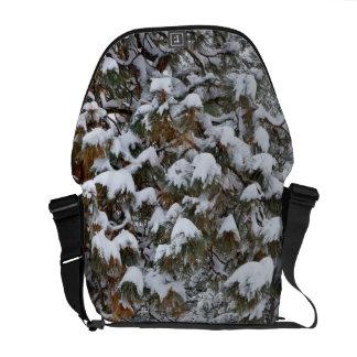 Snow fills the boughs of ponderosa pine trees messenger bag