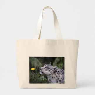 snow leopard sniffing flower tote bag