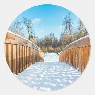 Snow on wooden bridge in forest classic round sticker