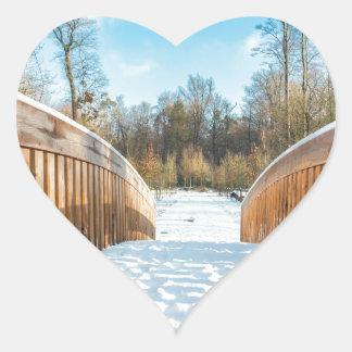 Snow on wooden bridge in forest heart sticker