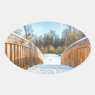 Snow on wooden bridge in forest oval sticker