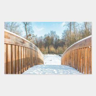 Snow on wooden bridge in forest rectangular sticker
