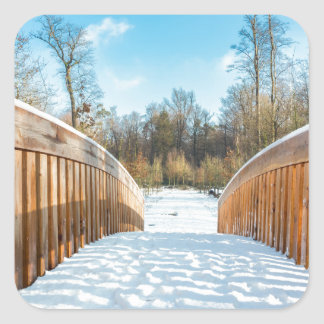Snow on wooden bridge in forest square sticker