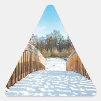 Snow on wooden bridge in forest triangle sticker