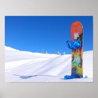 Snowboard en la nieve fresca, cielo azul póster